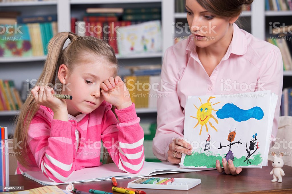 Female psychologist discussing drawing with a little girl stock photo