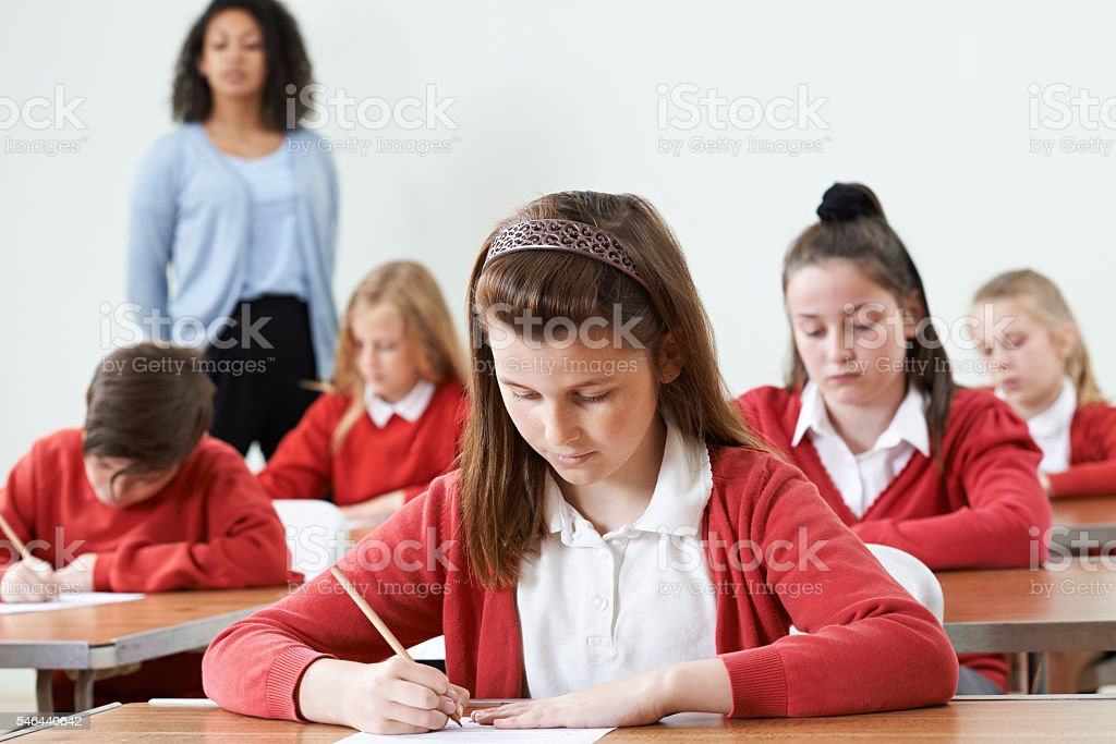Female Pupil At Desk Taking School Exam stock photo