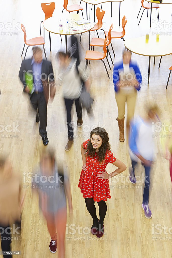 Female Pupil In Classroom Surrounded By Moving Students stock photo