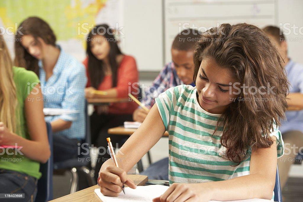 Female Pupil Studying At Desk In Classroom stock photo