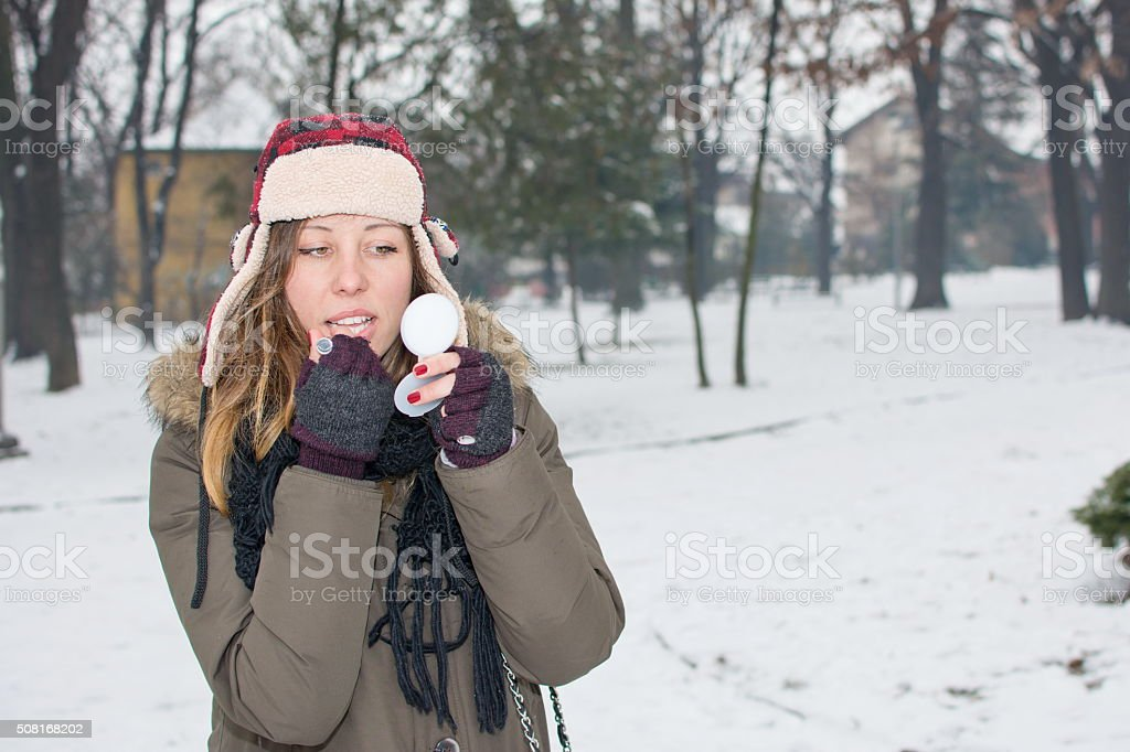 female putting on makeup in winter stock photo