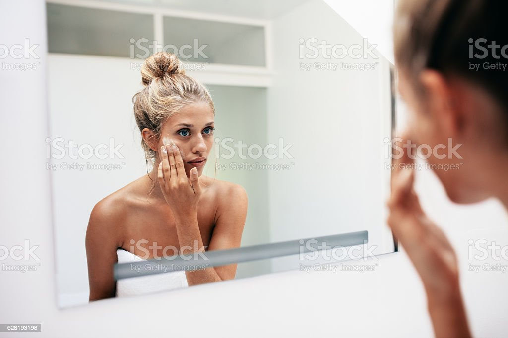 Female putting on moisturizer on her facial skin stock photo
