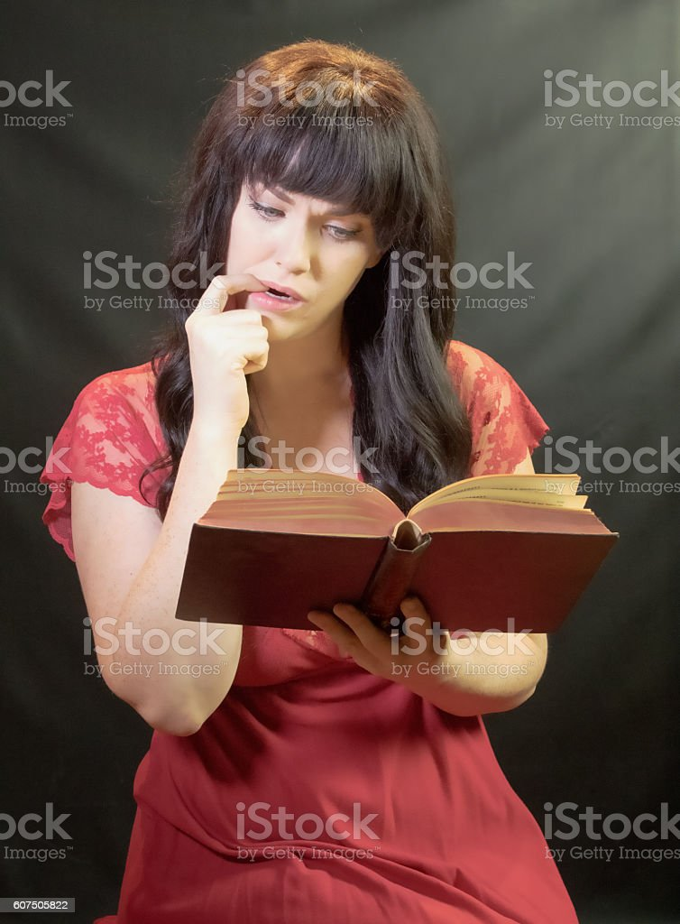 Female Puzzling Over A Book stock photo