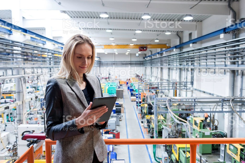 Female quality inspector using tablet stock photo