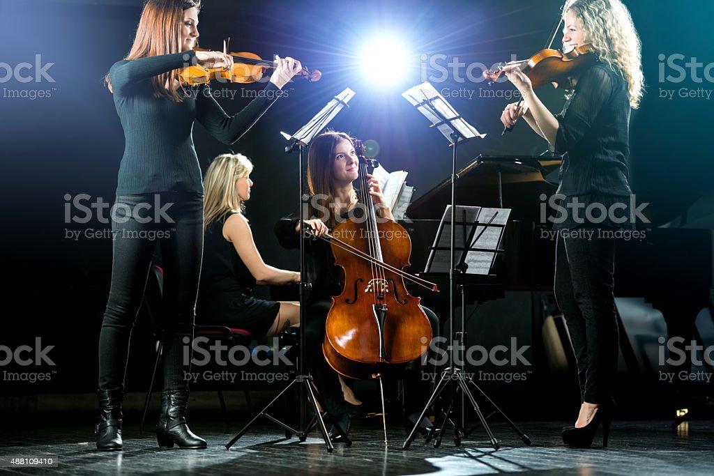 Female quartet playing music a rehearsal. stock photo