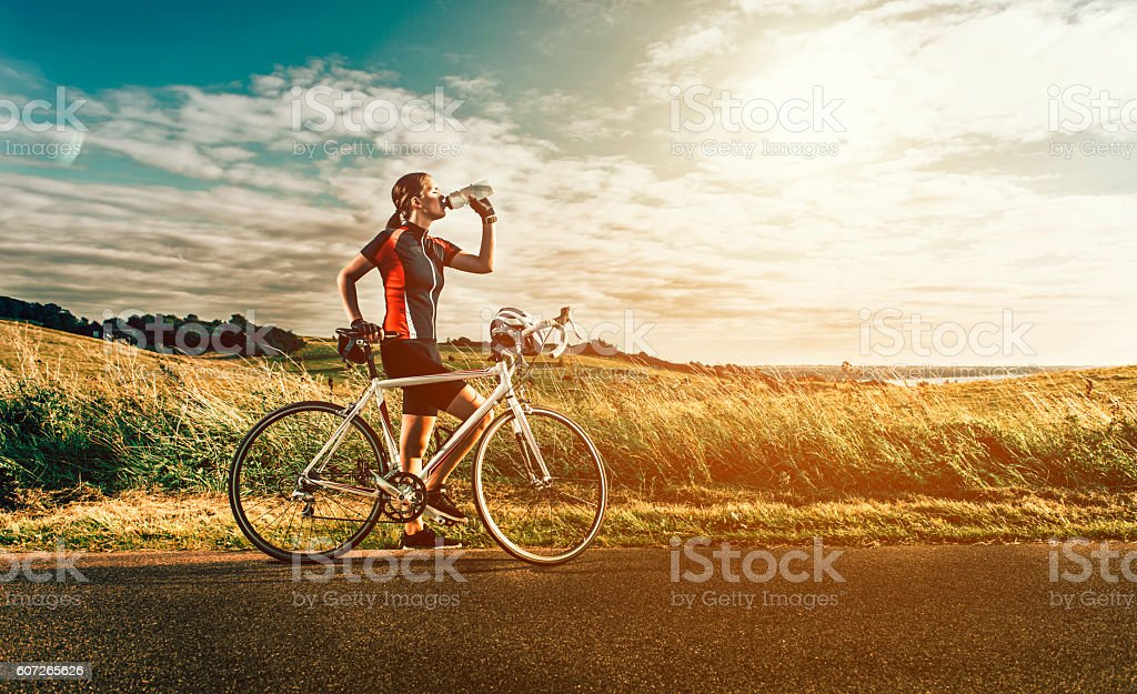 Female race cyclist stands next to bike near the sea stock photo