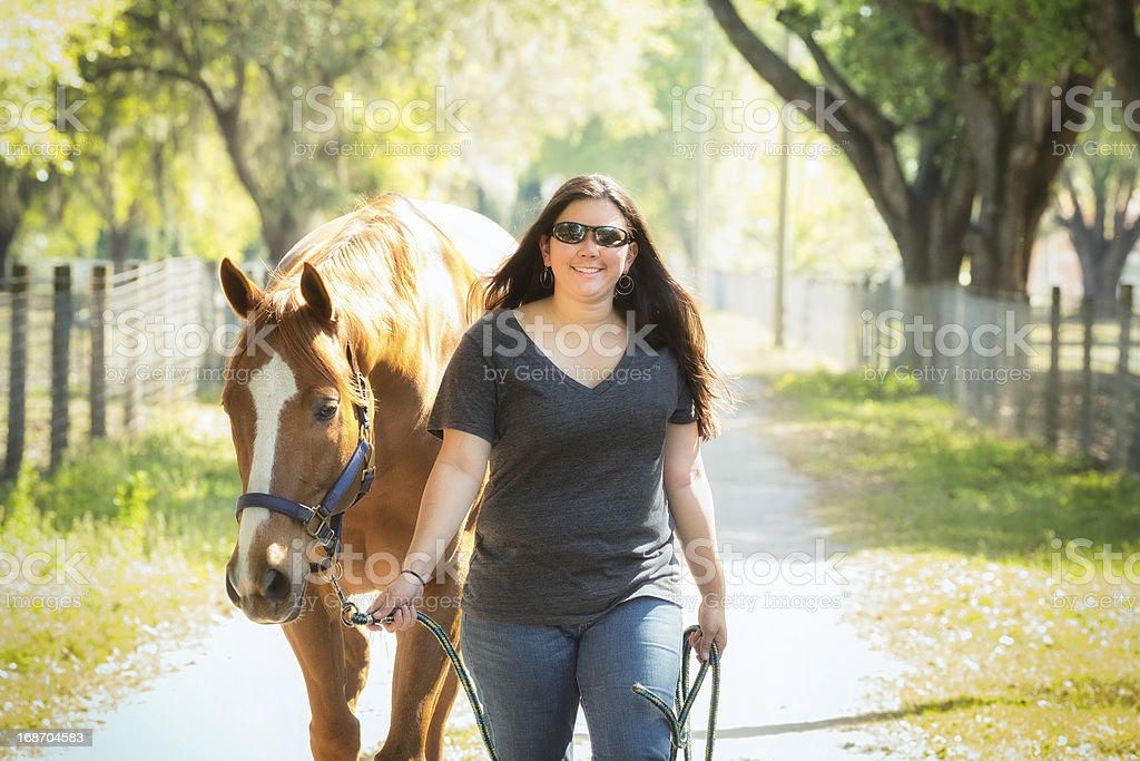 Female Ranch Employee Leading a Horse stock photo