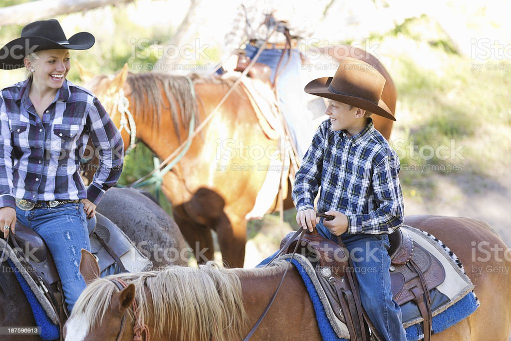 Female rancher riding horses with her young son royalty-free stock photo