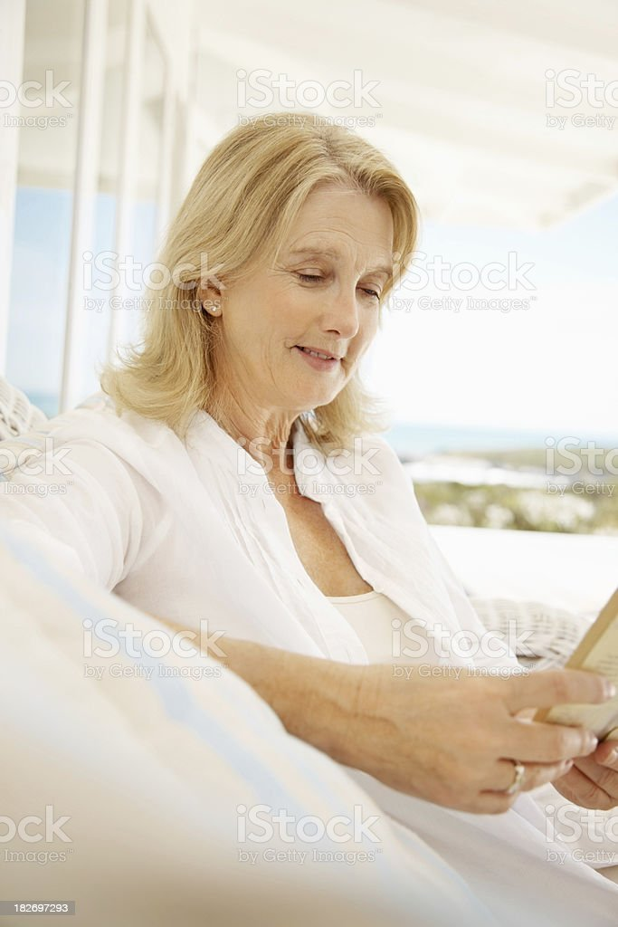 Female reading a book on couch at the porch royalty-free stock photo