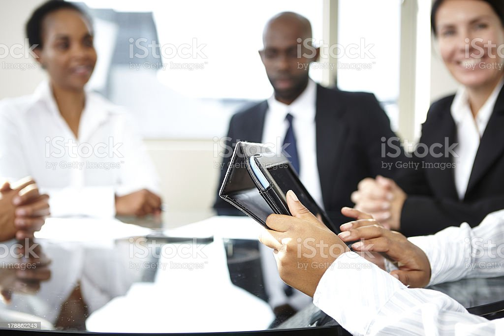 Female reads off mobile tablet during meeting stock photo