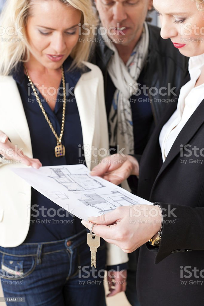 Female realtor explains lease agreement to a couple stock photo