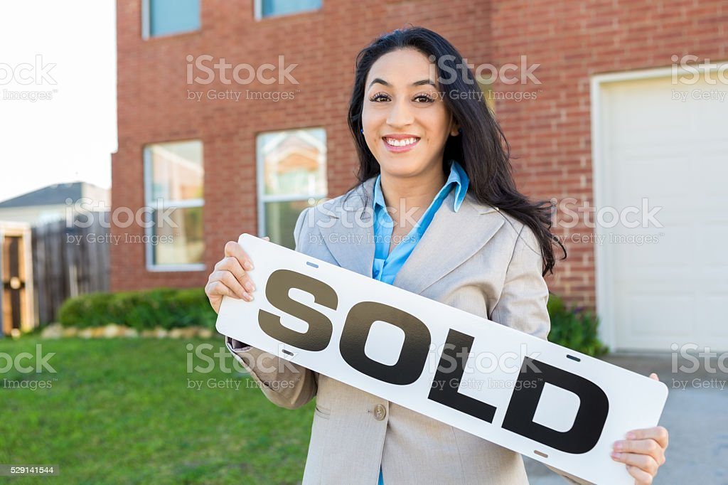 Female realtor or homeowner in front of new home stock photo
