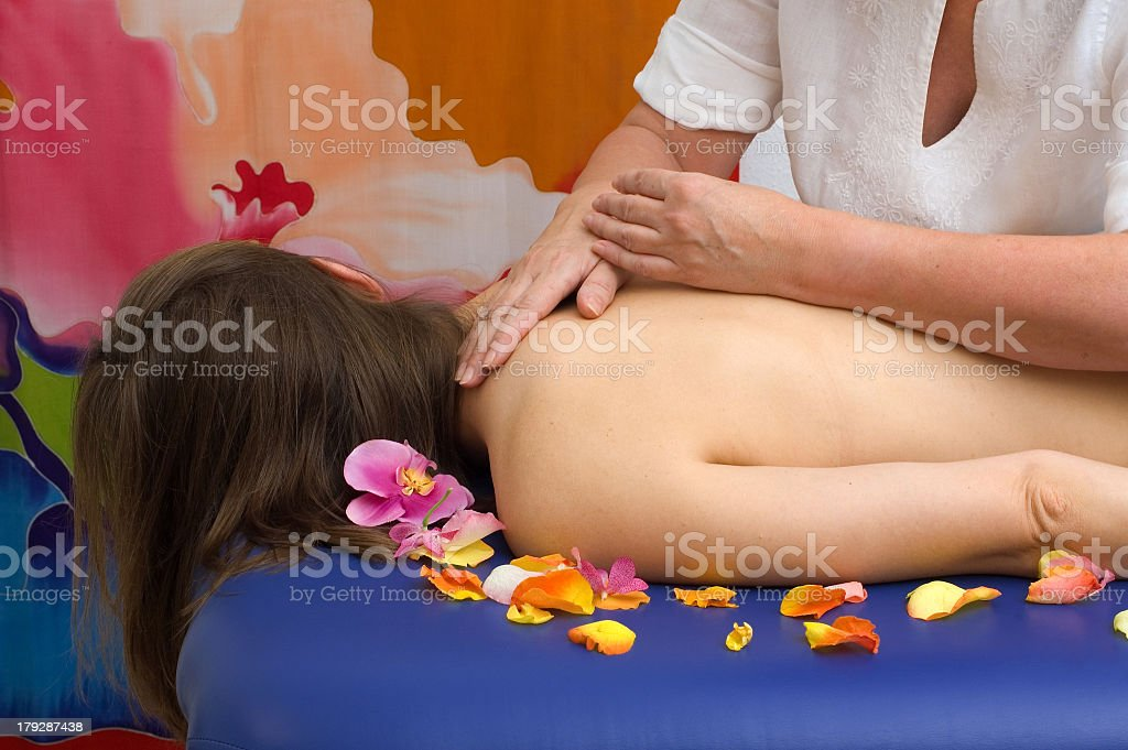 A female receiving a massage with tropical flowers stock photo