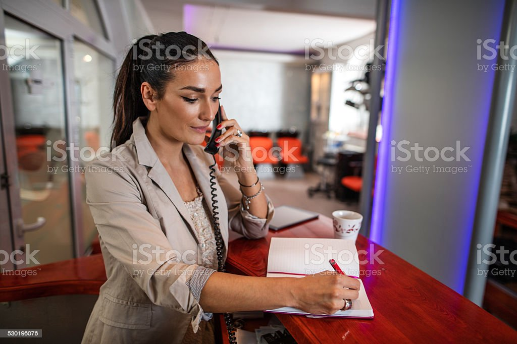 Female receptionist making appointment over the phone. stock photo