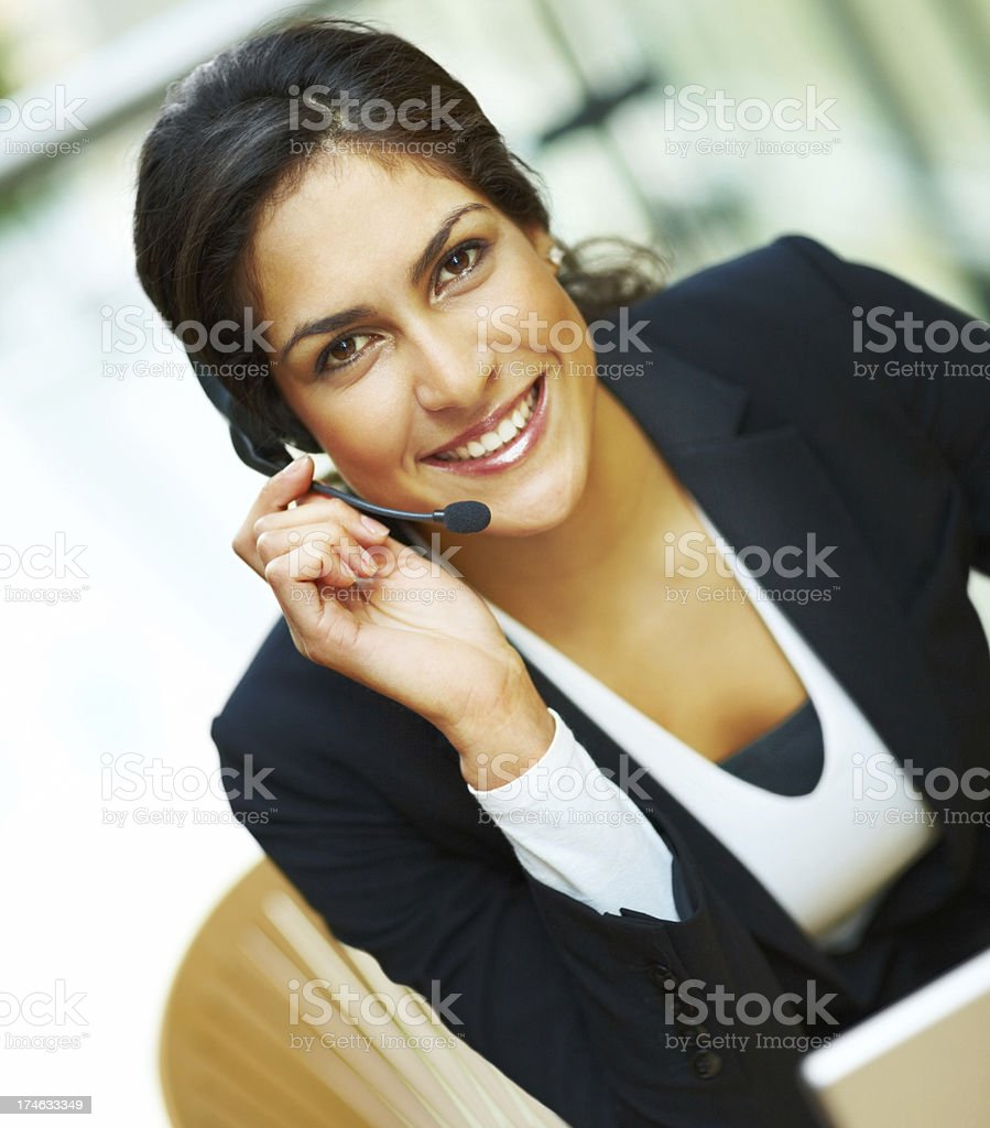 Female receptionist using headset and smiling royalty-free stock photo