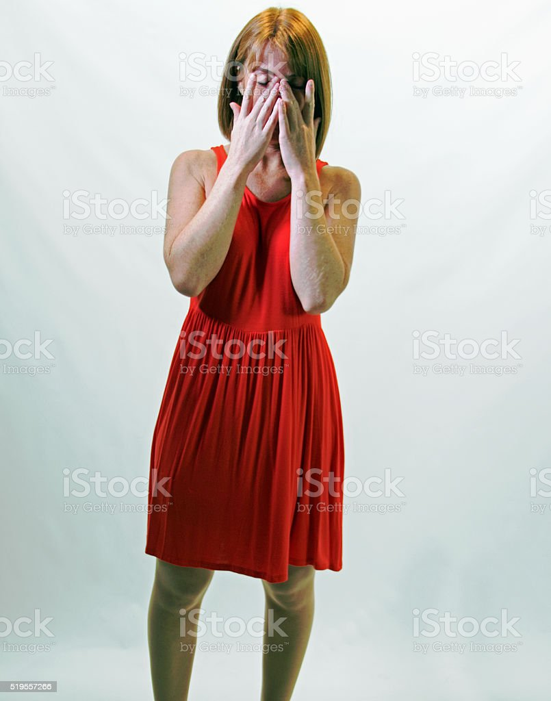 Female Red Head Wiping Away Her Tears stock photo