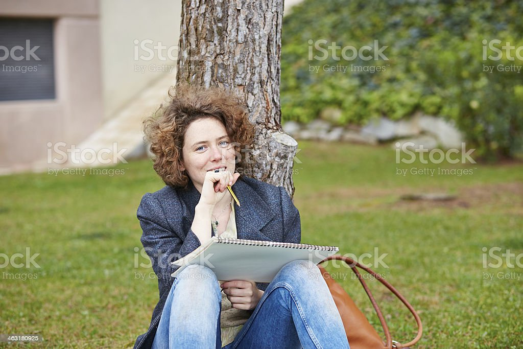 Female redhead art student drawing outdoors stock photo