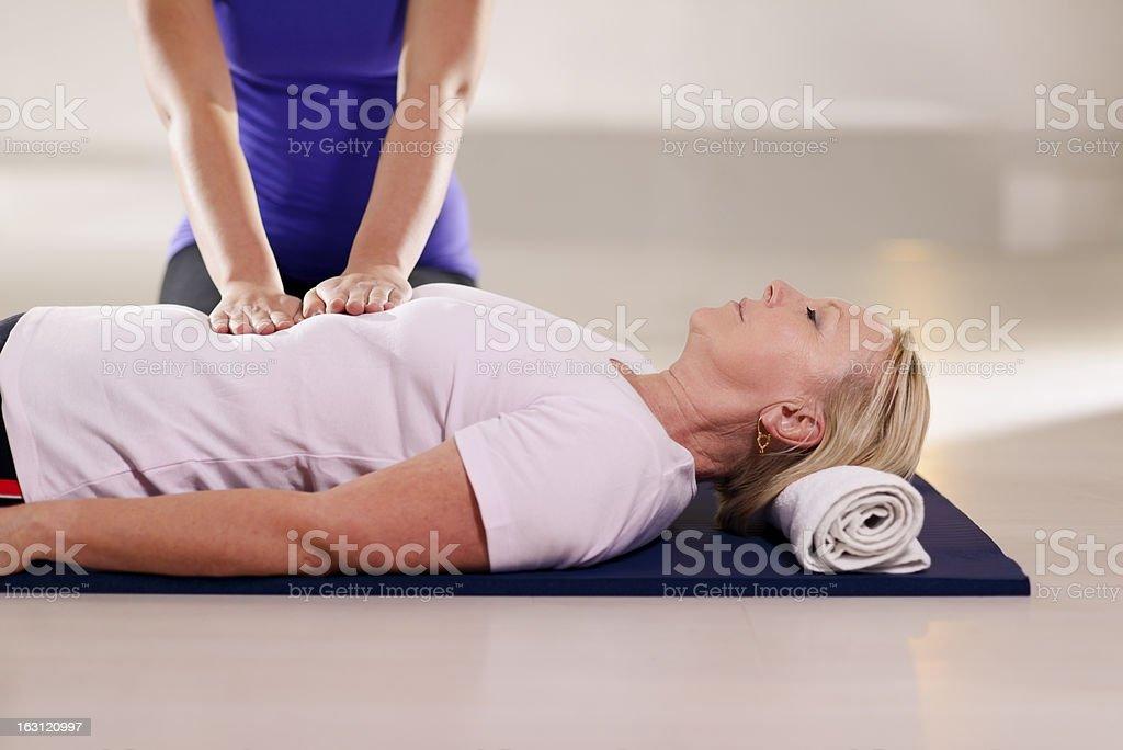 Female reiki therapist applying hands to older woman's torso stock photo