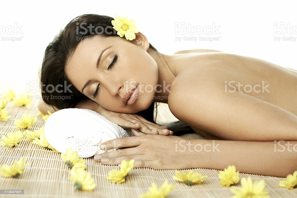 A female relaxing in spa surrounded by yellow flowers royalty-free stock photo