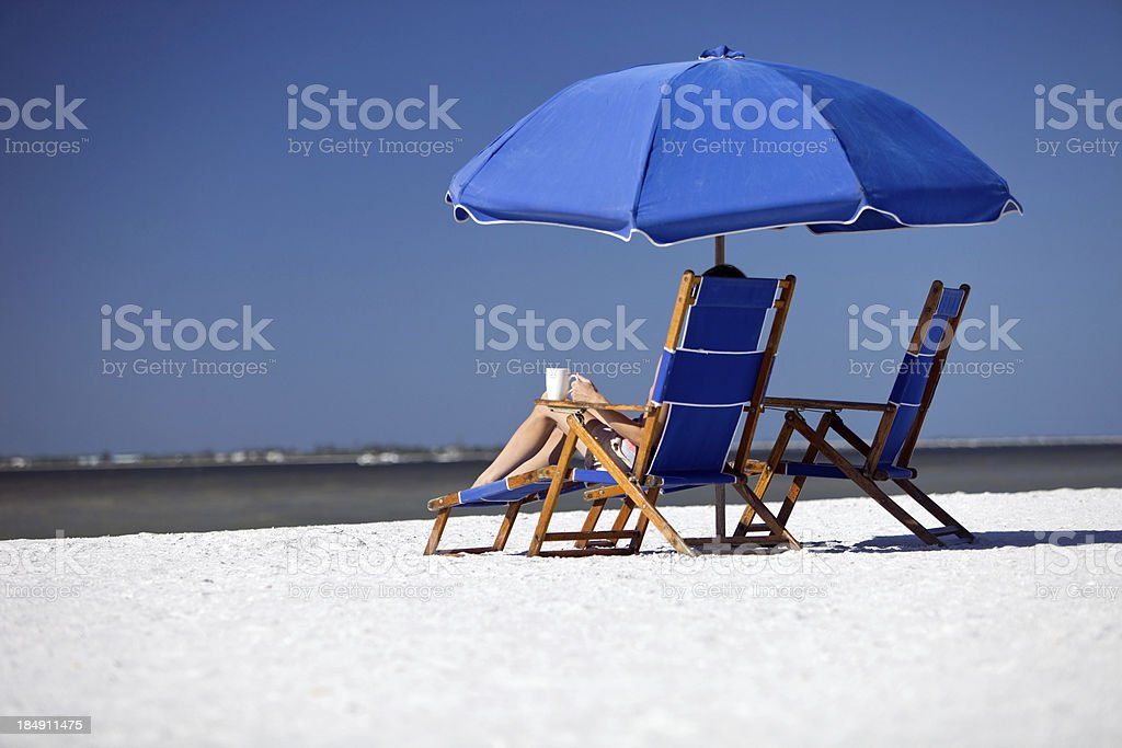 Female Relaxing on Beach Chair with Coffee Cup royalty-free stock photo