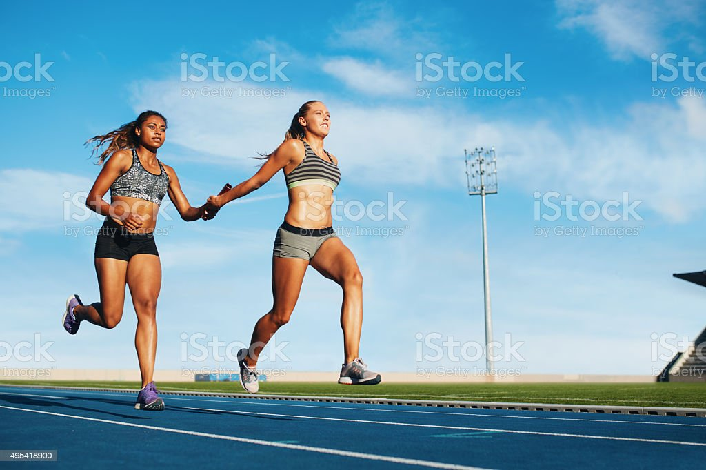 Female relay racing team on racetrack stock photo