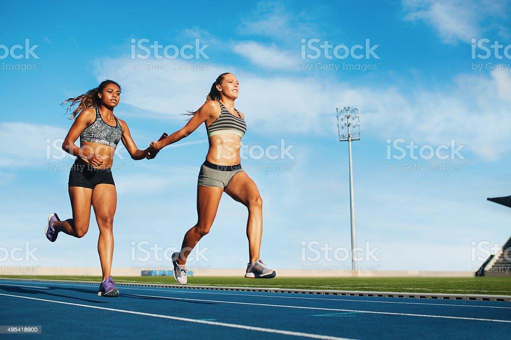 Female relay racing team on racetrack stock photo