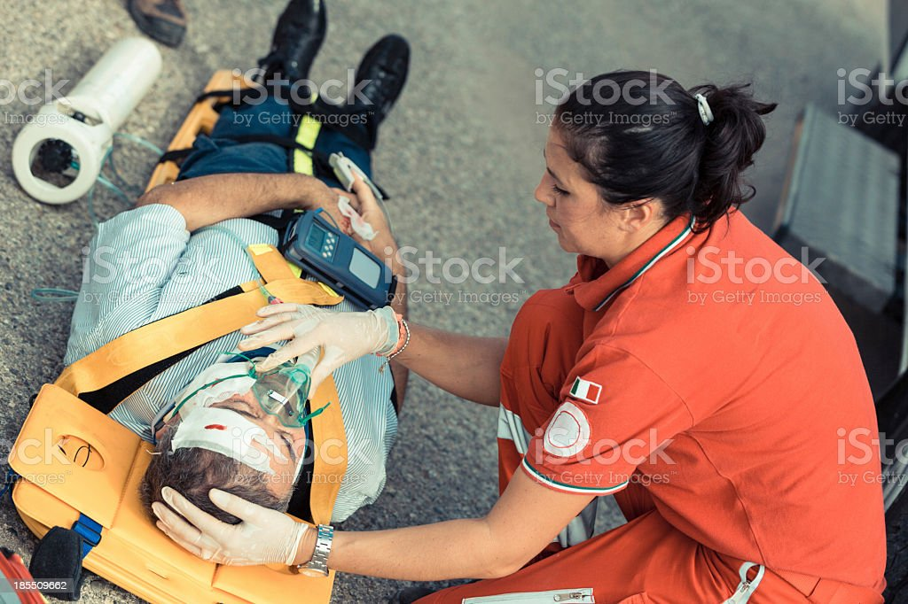 Female rescue team member gives First Aid to man on concrete stock photo