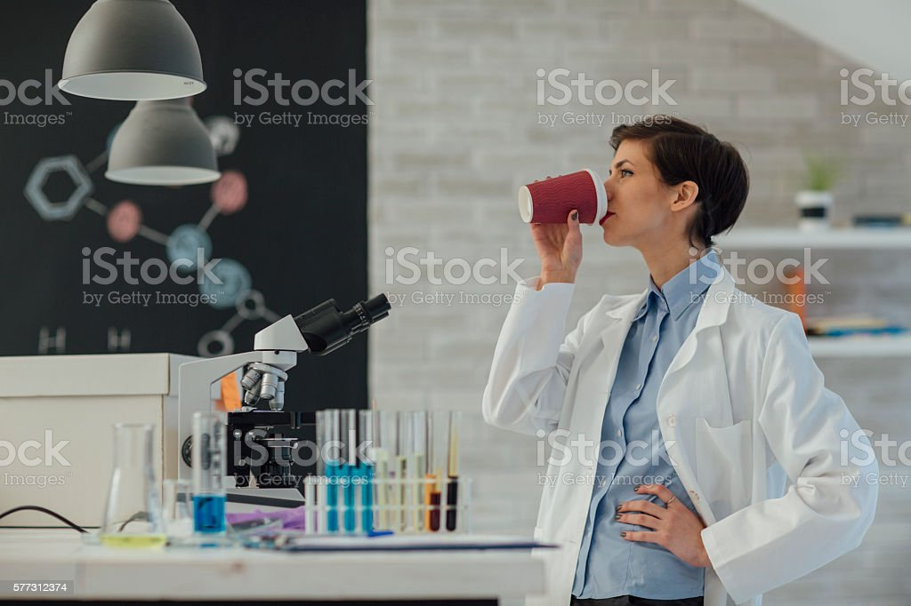 Female Researcher Drinking Coffee In Her Lab. stock photo