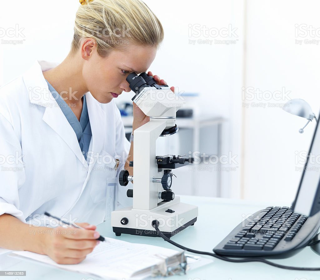 Female researcher looking into a microscope and writing notes royalty-free stock photo