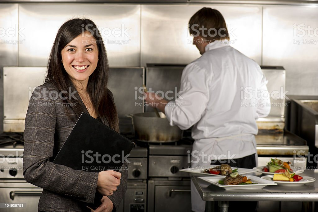 Female restaurant manager in kitchen with chef stock photo