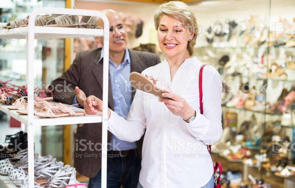 female retiree customer choosing pair of sandals in shoe store stock photo