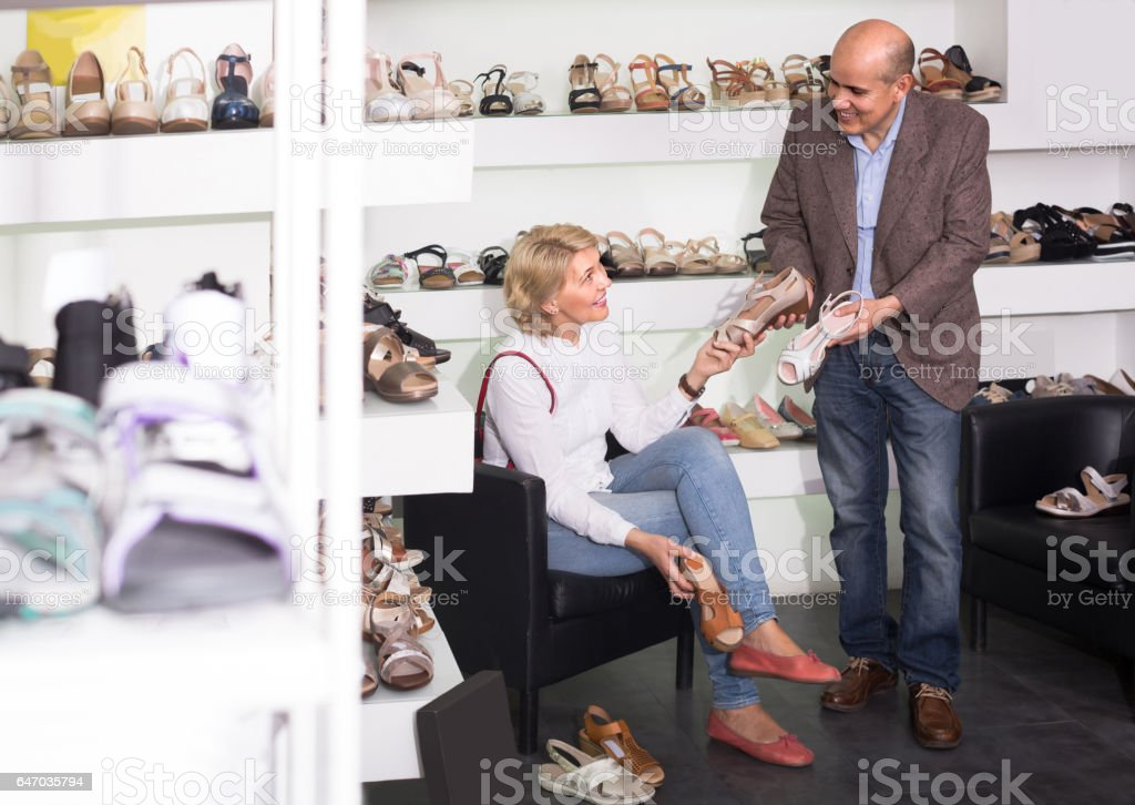 female retiree customer trying on pair of sandals stock photo