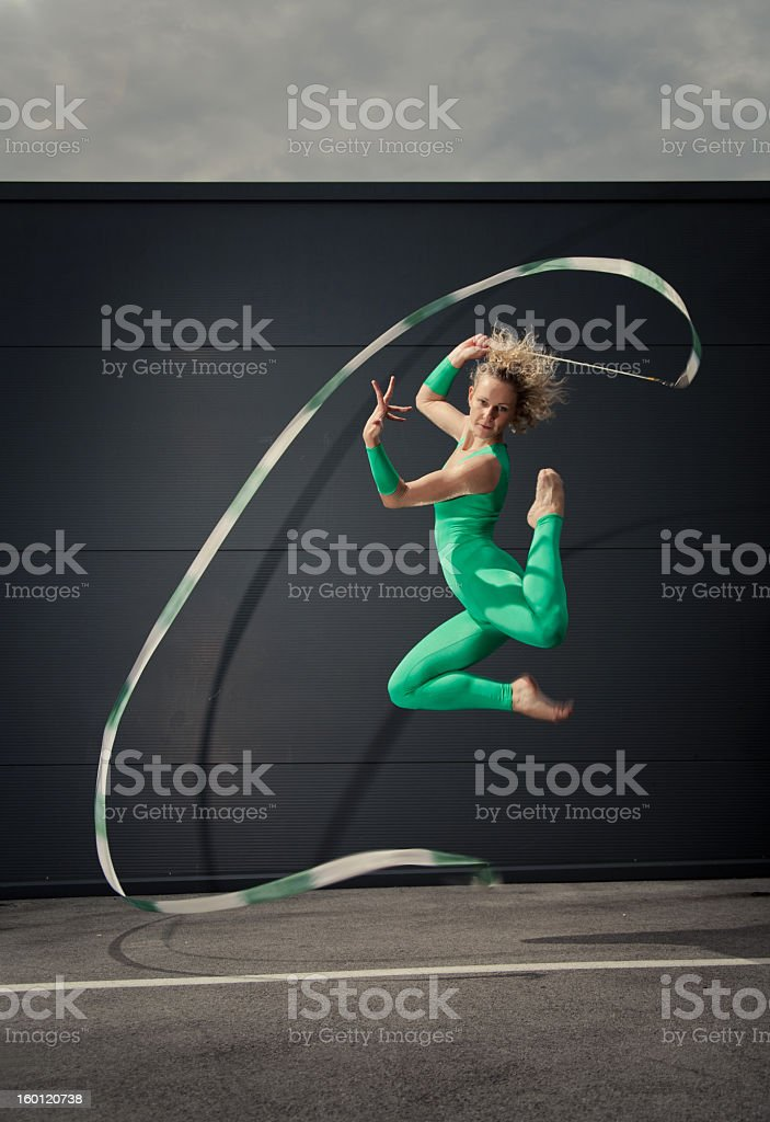 Female rhythmic gymnast in green jumps with long ribbon stock photo