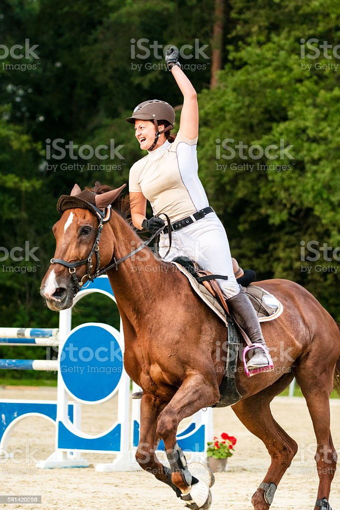 Female rider celebrates winning holding up hand stock photo