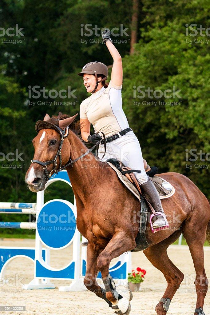 Female rider celebrates winning holding up hand stock photo