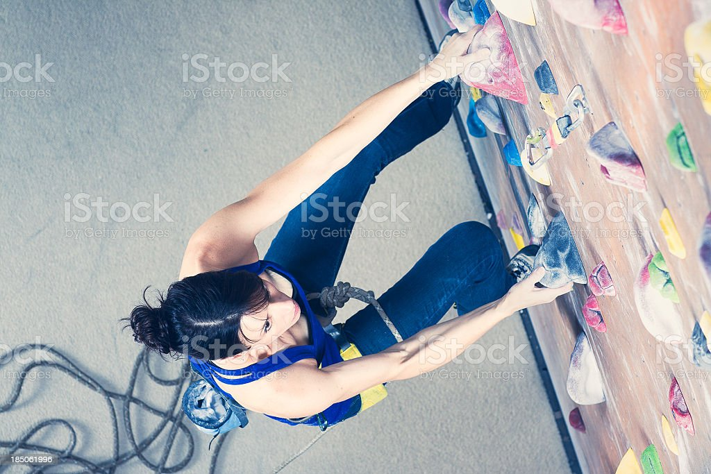 A female rock climber climbing a rock wall indoors stock photo