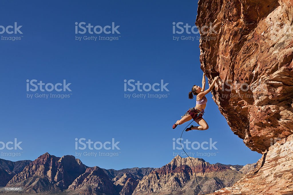 Female rock climber clinging to a cliff. stock photo