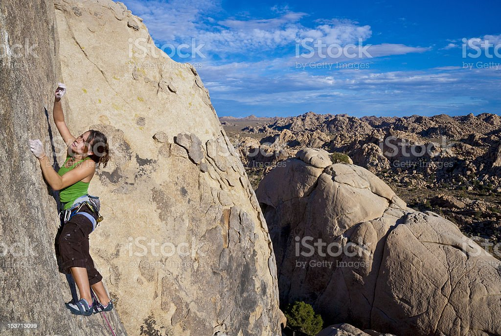 Female rock climber clinging to a cliff. royalty-free stock photo