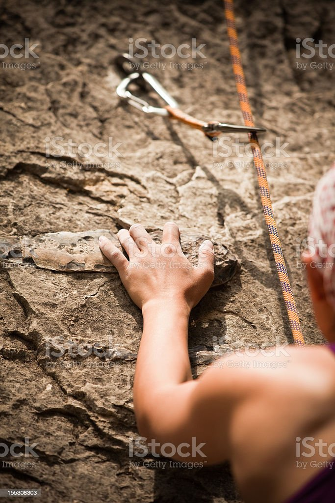Female Rock Climber grasping at hand hold royalty-free stock photo