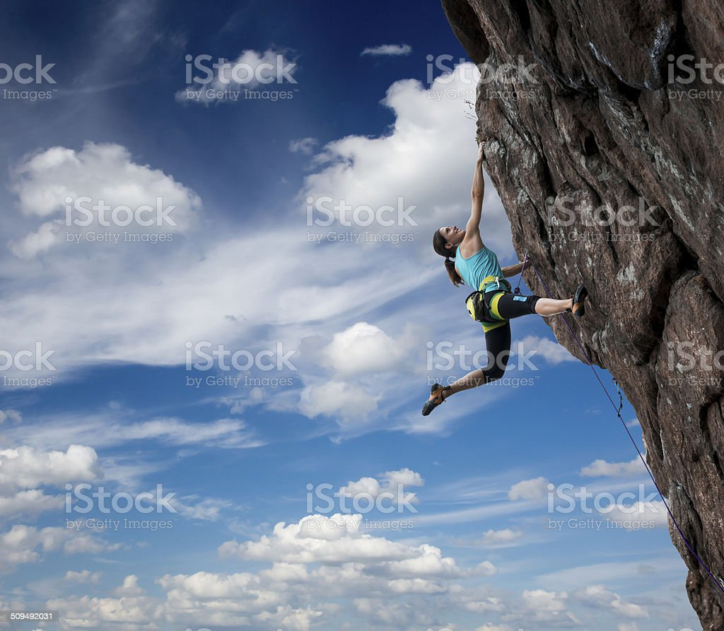 Female rock climber hanging over the abyss stock photo
