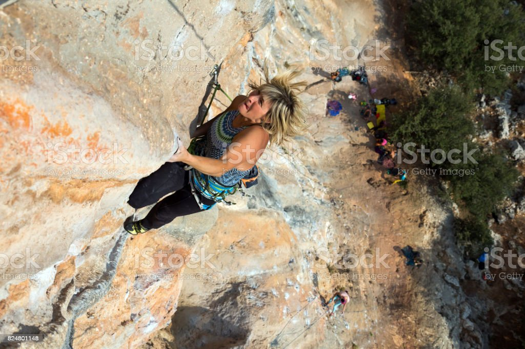 Female Rock Climber makes a difficult move on overhanging Wall stock photo