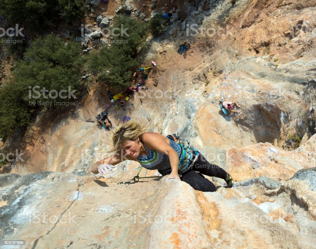 Female Rock Climber makes difficult move vertical Wall top View stock photo