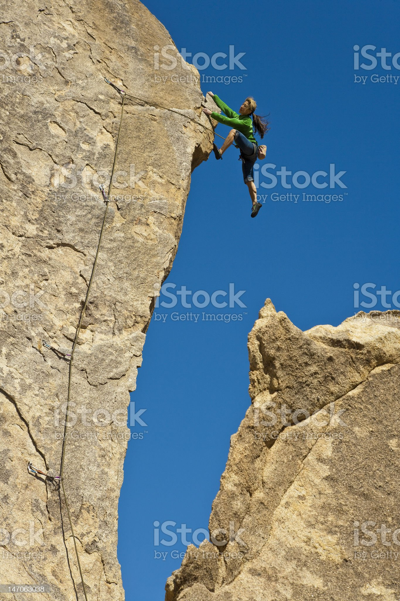 Female rock climber on a cliffside with blue sky in the back royalty-free stock photo