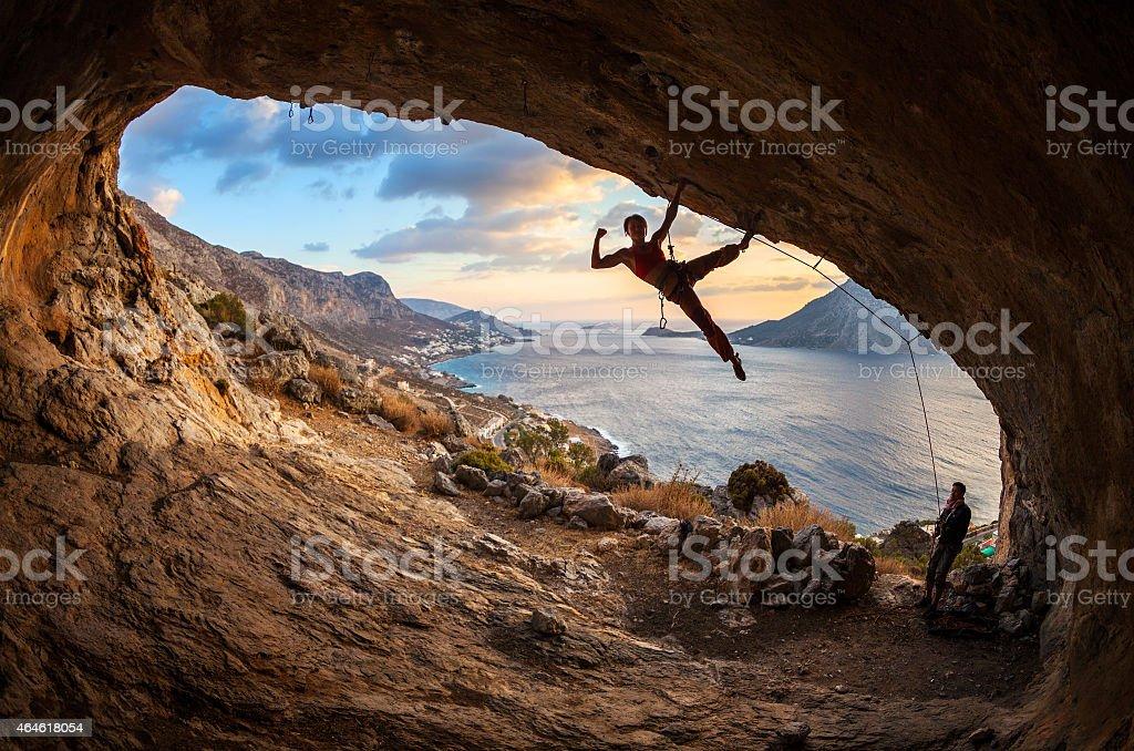 Female rock climber posing while climbing stock photo