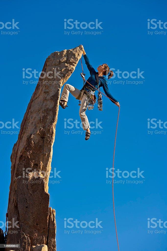 A female rock climber reaching the summit stock photo