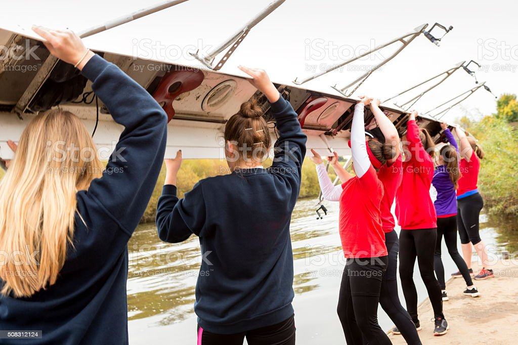 Female rowing team put their boat in the water stock photo