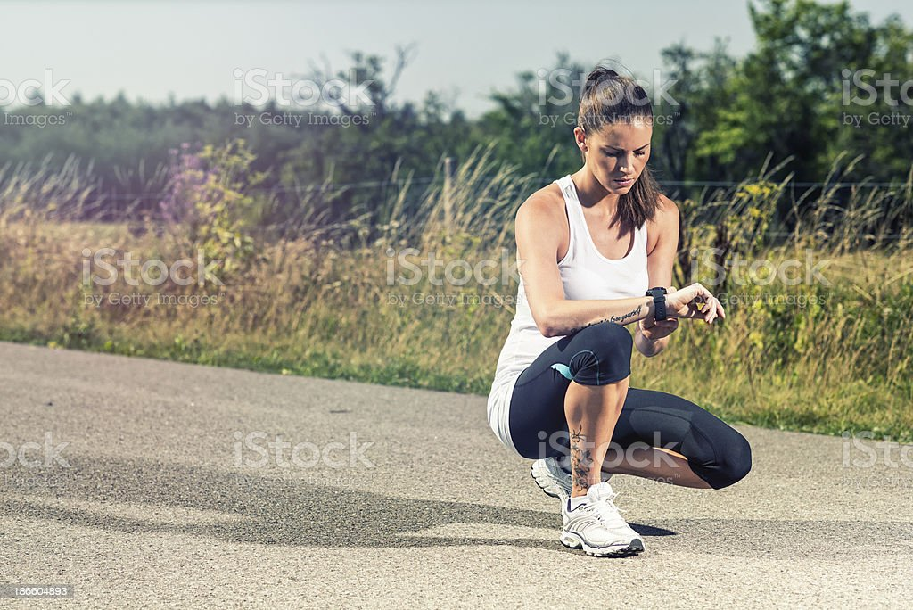 Female runner is using a pulse or GPS watch royalty-free stock photo