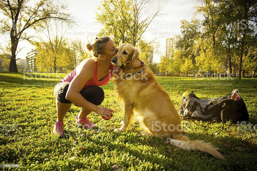 Female runner kissing her dog, in the park royalty-free stock photo