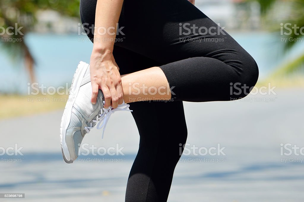 Female runner leg and muscle pain during running outdoors stock photo