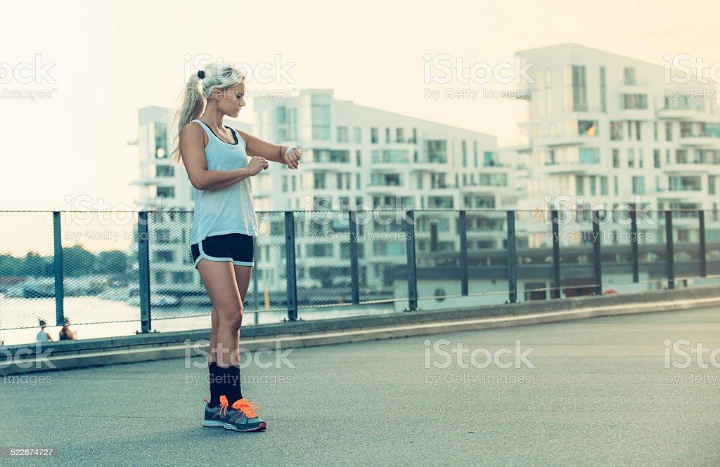 Female runner looks a GPS watch before run stock photo